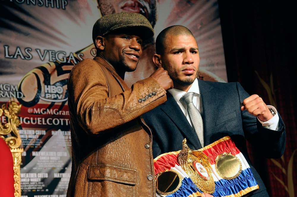 Floyd Mayweather Jr. and Miguel Cotto pose for some shots at the press conference to promote their Junior Middleweight championship bout in Las Vegas.