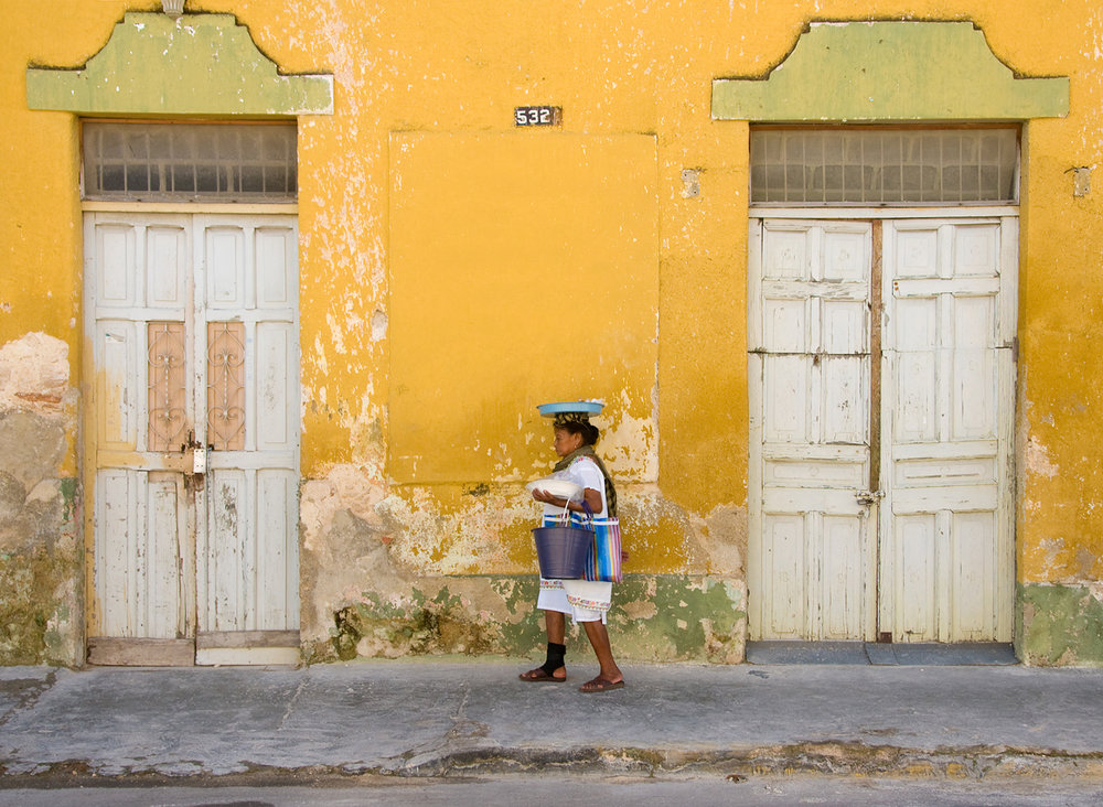A woman takes a Sunday stroll through the colonial streets of Mérida, Mexico. On any given day here, you can encounter a living, breathing canvas of eye-pleasing color contrasts, old world architecture and traditional Mayan customs blending seamlessly with a festive and ever-casually buzzing modern-day city life...a sensory collective that is undoubtedly enhanced by the savory scent of salbutes and panuches on every street corner.