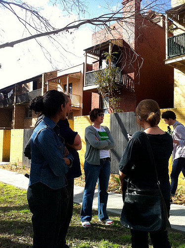 Key Project member and local Woolloomooloo resident- Stacey Miers (in the green bans t-shirt) discusses some of the history of the housing around Sir Dennis Winston Place.