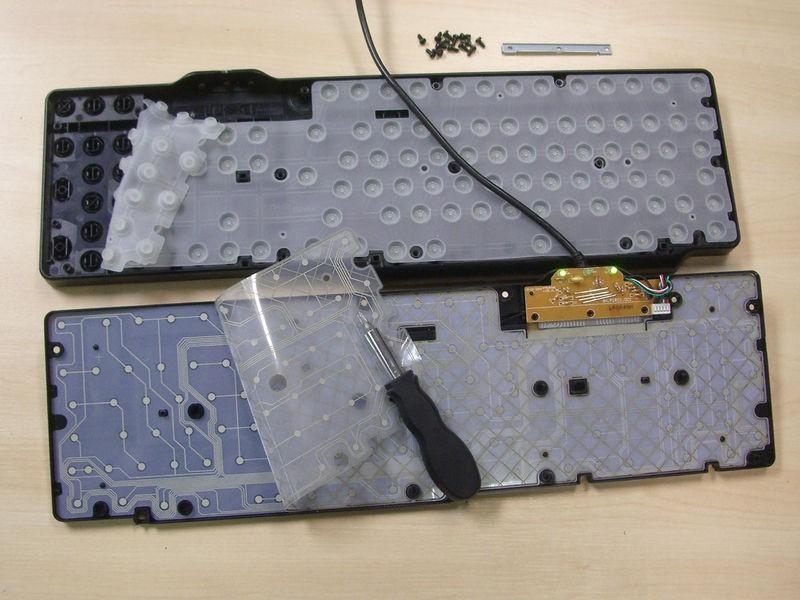 Teclado de membrana aberto no meio (de um lado, a parte das teclas e os contatos, de outro, a parte de baixo do teclado e a membrana do teclado)