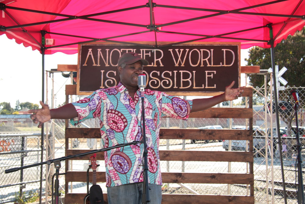 Bruce Rhodes - Bruce Alan Rhodes was born in New York City in 1954. Raised in The Todt Hill Projects, he formulated the belief early in life that family, community, and environment were the foundation of a positive world.  Connecting cultures and service-projects in Santa Rosa to those in West Africa Bruce spearheads the non-profit Drums for Solar.
