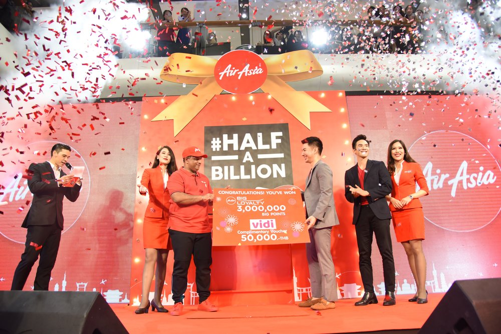 AirAsia's 500 millionth guest Dr Panut Oprasertsawat (centre right) receiving 3 million AirAsia BIG Points, THB50,000 worth of Vidi vouchers and free AirAsia flights for life from AirAsia Group CEO and AirAsia X Co-Group CEO Tony Fernandes and Thai TV superstar Pope Thanawat (second from right).