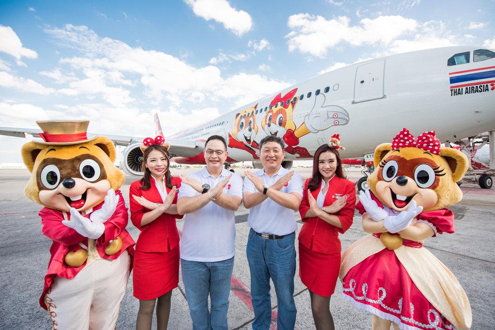 """นายนัตดา บุรณศิริ ประธานเจ้าหน้าที่บริหารสายการบินไทยแอร์เอเชีย เอ็กซ์ (กลางซ้าย) นายดงกิ ปาร์ค (Dong Ki, Park) ประธานเจ้าหน้าที่บริหารลอตเต้เวิลด์ (กลางขวา) ร่วมถ่ายภาพกับเครื่องบินลาย """"Lotte World"""" เมื่อวันพุธที่ 5 กันยายน 2561 ณ ท่าอากาศยานดอนเมือง เพื่อเป็นการฉลองความสัมพันธ์ร่วมกัน"""