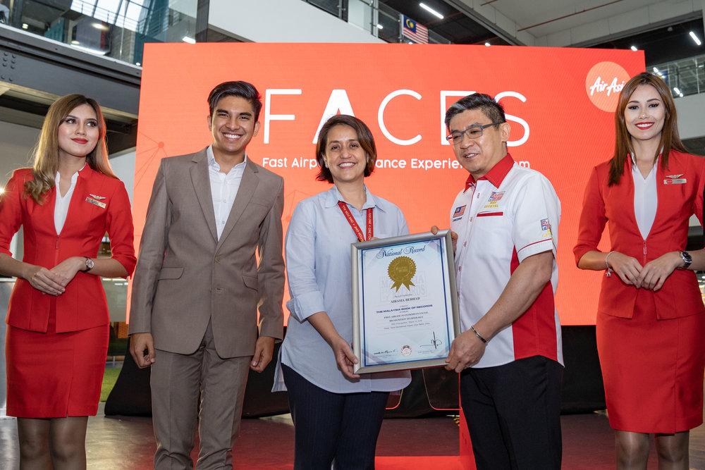 Kenyataan Gambar: (Dua dari kanan) Ketua Pegawai Operasi Malaysia Book of Records Wong Hong Wai menyampaikan sijil pengiktirafan untuk FACES kepada Timbalan Ketua Pegawai Eksekutif AirAsia (Digital, Transformasi dan Perkhidmatan Korporat) Aireen Omar, dan disaksikan oleh Menteri Belia dan Sukan Malaysia YB Syed Saddiq Syed Abdul Rahman   di ibu pejabat AirAsia, RedQ, hari ini.