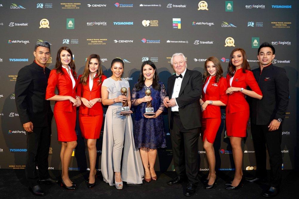 亚航集团空服员总监Suhaila Hassan(左中)与亚航集团通讯总监Audrey Progastama Petriny从世界旅游将主席兼创办人Graham Cooke(右中)接过世界领先低成本航空奖及世界领先低成本航空空服员奖。
