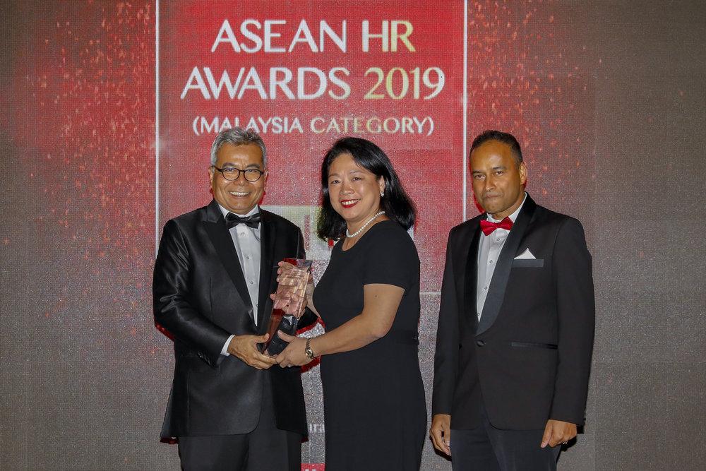 (左起)企业家发展部长拿督斯里Mohd Redzuan Md Yusof于Asean HR Awards 2019颁奖典礼上将奖座颁给亚航办公室设施主管郭德玲,同时由Niagatimes顾问Dato' R. Rajendran见证。