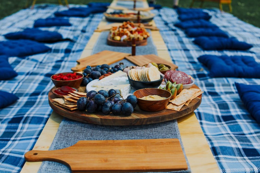 PICNIC FOR 8 - 10 PEOPLE - Settle into a beautifully styled picnic at Princes Park in Carlton. We provide an extra large picnic blanket, picnic basket, seat cushions for all guests and a row of low folding tables. This package comes with 2 large platters filled with cheese, cured meats, crisp breads, fruits, nuts and condiments. Additionally, we provide a medium platter filled with seasonal fruits, a small dessert platter, 2 large bottles of San Pellegrino sparkling water and 4 bottles of sparkling Rosé. All of our picnics come with complementary picnic games.