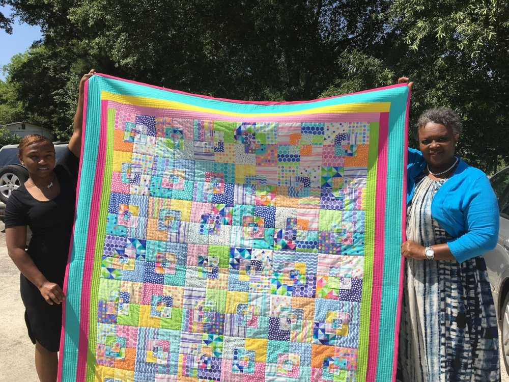 Deborah Sherer (right) displays her specially-made quilt along with her cousin, Tiangela Sherer.