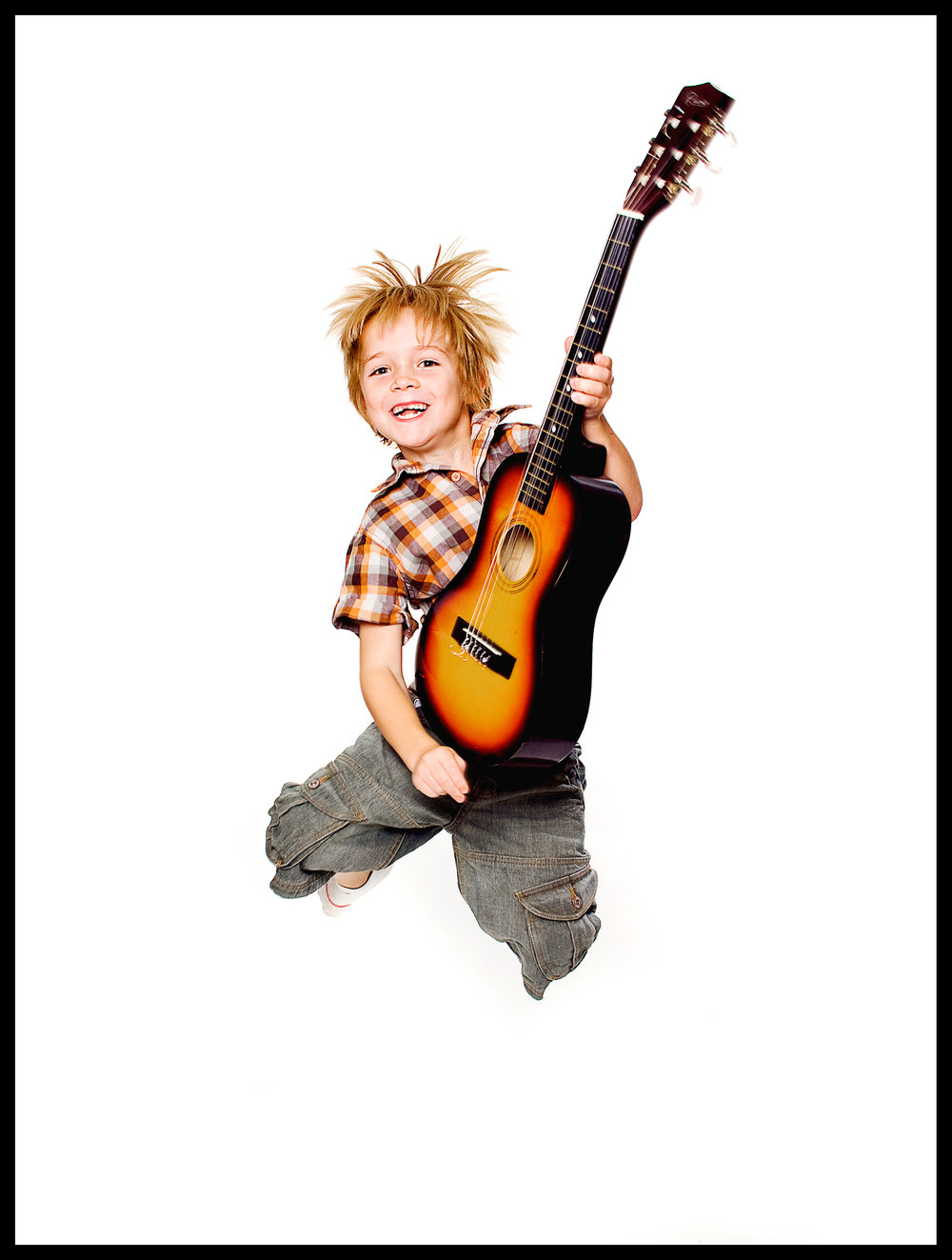 portrait of blonde boy with a guitar jumpin
