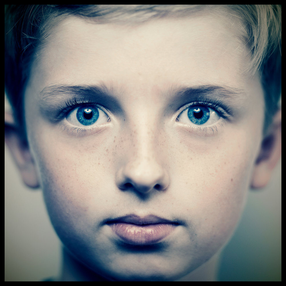 blue eyed boy close up photograph