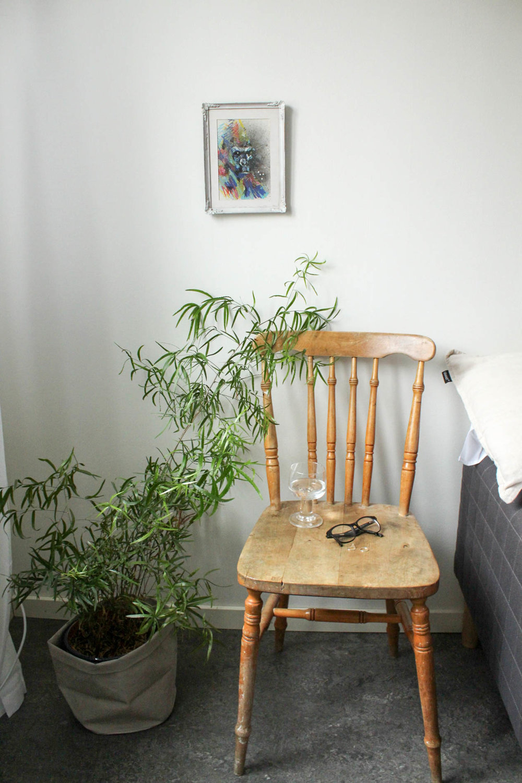 """Den här stolen hade en sliten (och ganska ful) sittdyna, men den är så mycket finare när man ser det slitna sätet. Det får vikariera som nattduksbord. Tavlan med gorillan fick jag av en graffitimålare jag dejtade innan jag skulle flytta till USA (""""man kan behöva en gorilla som tar hand om en"""")."""