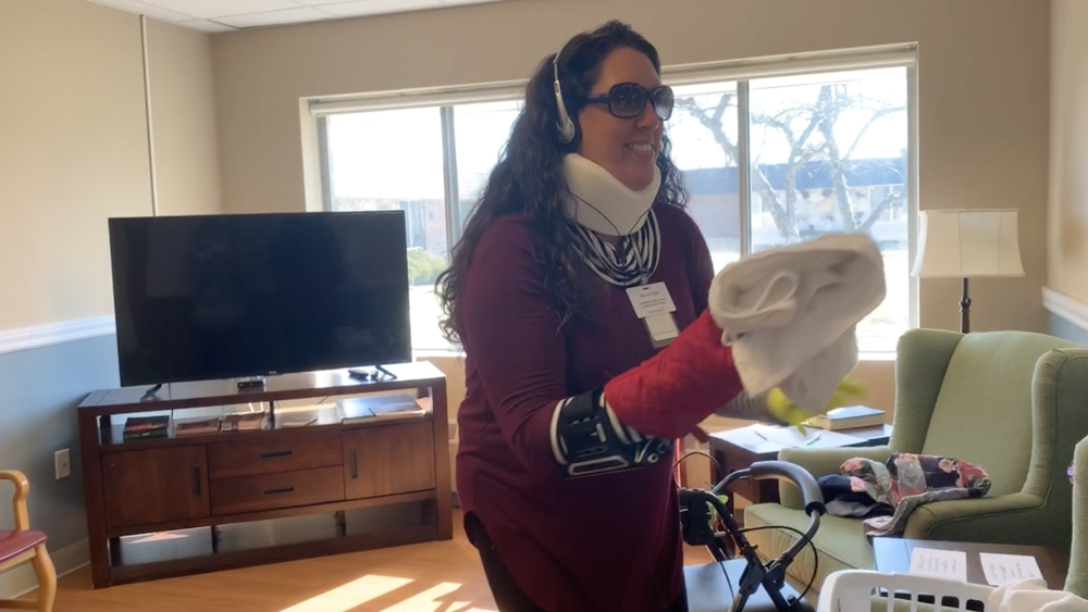 SKLD Zeeland staff member attempts to fold laundry during a dementia simulation training session.