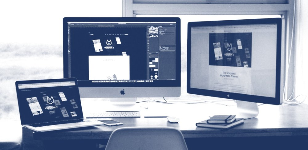 Three Computer Monitors in a Workplace Setting Showing a Graphic Design Project in Progress