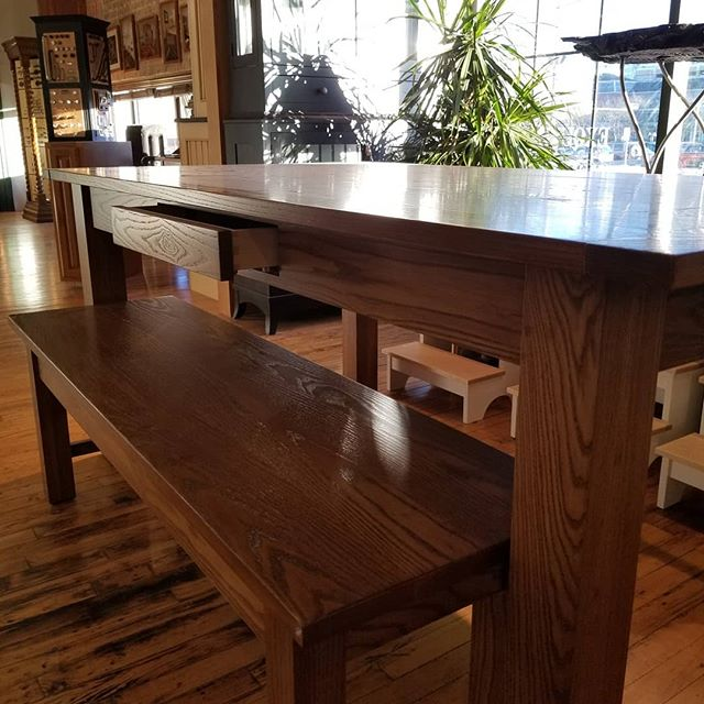 This ash table and bench are sitting pretty in our showroom, waiting to go home for the holidays! 🎅🤶 We think the apron drawer is pretty slick too! . . . Homestead Cabinetmakers  Custom Furniture & Cabinetry made in downtown Kalamazoo, Michigan. . . www.welovewoodworking.com . . . #ash #woodfurniture #customtable #woodshop #woodworkersofmichigan #puremichigan