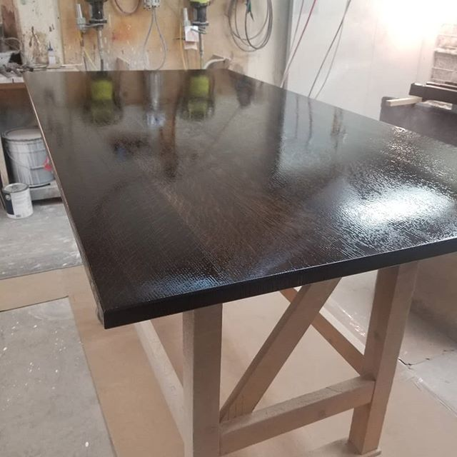 First coat of lacquer freshly sprayed on this quarter sawn white oak table top. It'll be ready for final assembly in the morning, then off to the showroom! . . . Homestead Cabinetmakers  www.welovewoodworking.com  Custom Furniture & Cabinetry made in downtown Kalamazoo, Michigan . . . #woodworkersofmichigan #customwoodwork #customfurniture #customcabinets #woodshop #femalewoodworkers #madeinmichigan #madeinkalamazoo #finewoodworking #finishworks #table #craftsman