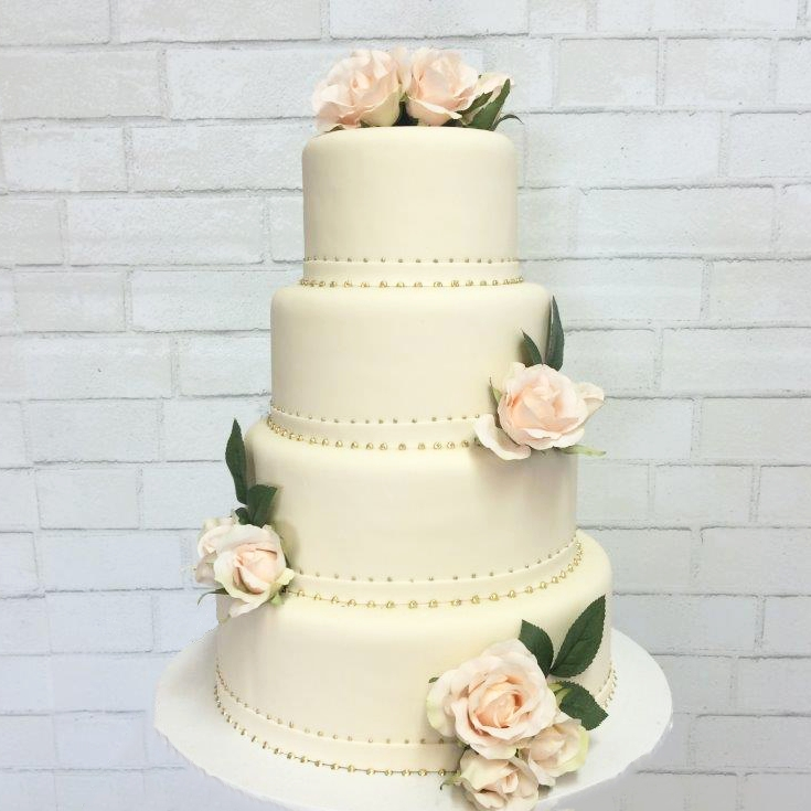 Katella Bakery four tear wedding cake with real flower arraignments