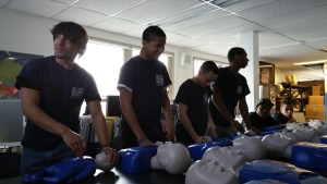 Michael, Akeem, Justin, and Mohammed practice CPR on infant manikins
