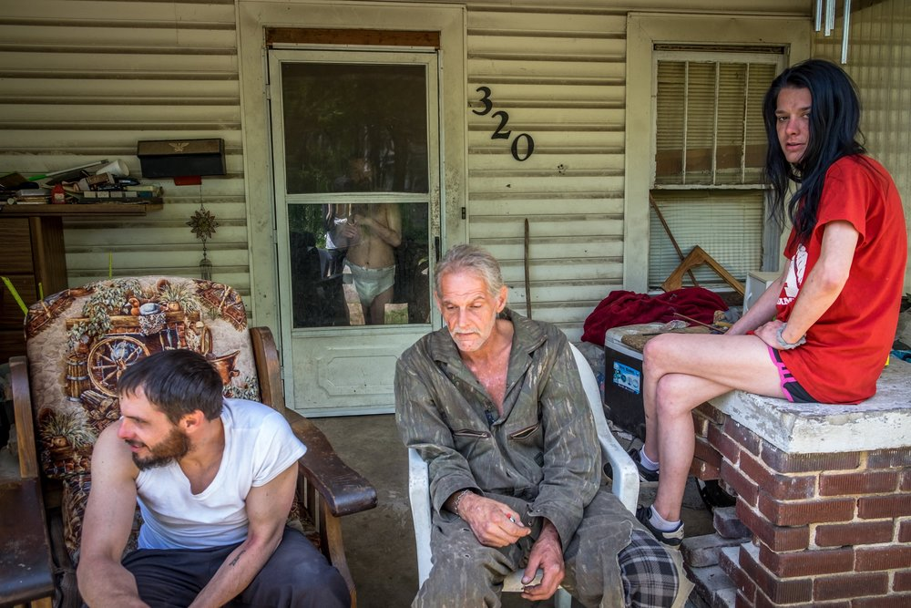 This was my first day meeting Craig, J.B., Mama & Angel. I drove by and they were sitting just like this. I turned the car around as fast as I could, pulled up in front of there house and asked if I could make a picture of them sitting there. I heard yelling coming from inside the house, almost panic screams and as I was shooting this photo, a new character emerged from the shadows and into the doorway