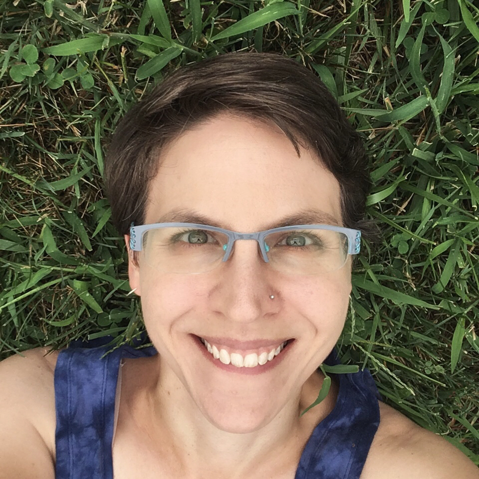 [image description: head-and-shoulders picture of me, a pale person with short brown hair and gray glasses, lying in the grass and smiling at the camera.]