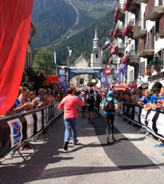 Sandy (in the blue cap) headed for the UTMB finish. That's her husband, Colin (in the red shirt), chasing after her with the camera.