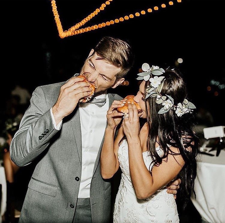 Couple eating burgers at wedding