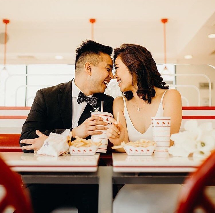 couple eating burgers after wedding