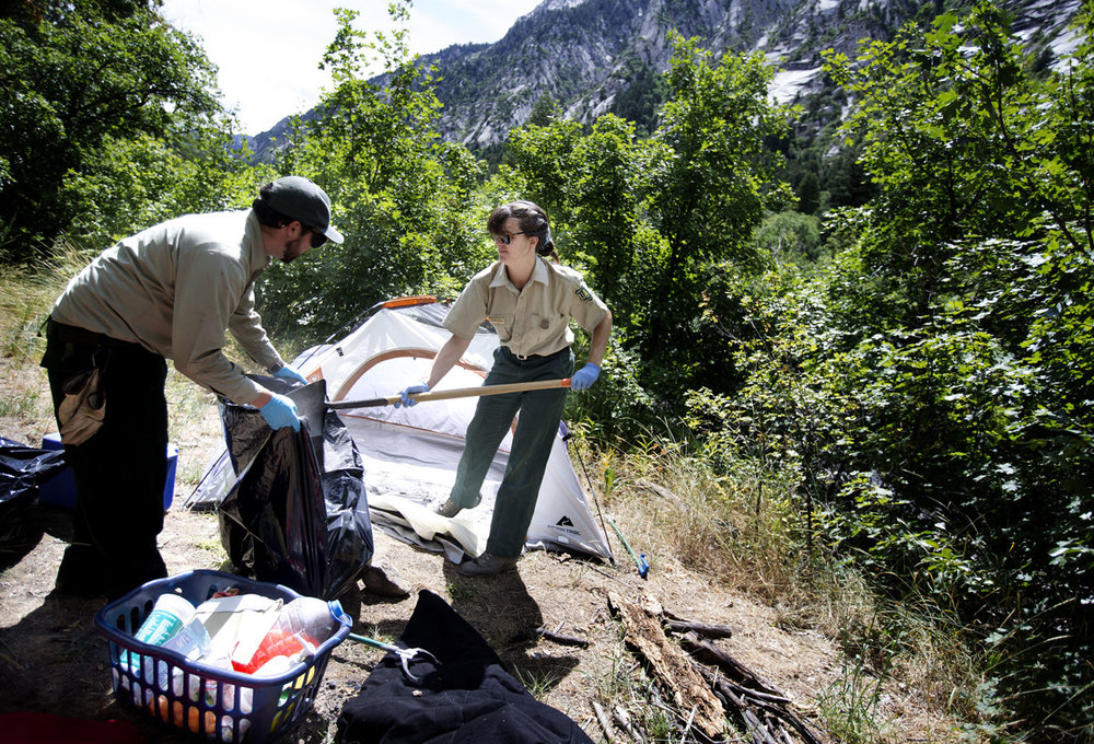 Justin Hurtt and Meghan Stan, trail crew members with the U.S. Forest Service's Salt Lake Ranger District, pick up garbage from an abandoned campsite in Big Cottonwood Canyon on Friday, June 29, 2018. Courtesy of  Deseret News.