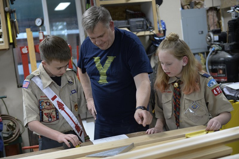 Darwin Cook, Deseret Peak District Chairman with the Great Salt Lake Council,Boy Scouts of America offers guidance to his son Kolbie, 12, as he works on a merit badge with a little help from his sister Miriam, 11, in the family garage in Tooele, Utah, on Monday, May 14, 2018. Miriam who always wanted to enlist in her older brother's troop is among the first wave of girls joining the Boy Scouts of America in two all-girl dens near Salt Lake City. Miriam Cook of Tooele has already earned 11 Webelos advancements in her first 3 months as a Cub Scout with the pack based in Taylorsville. (Francisco Kjolseth/The Salt Lake Tribune via AP)