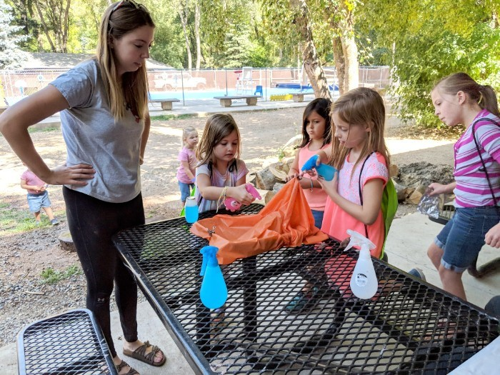 Ambassador Kendall FitzGerald helps campers build their own mini watersheds. (Photo via  STEMAP