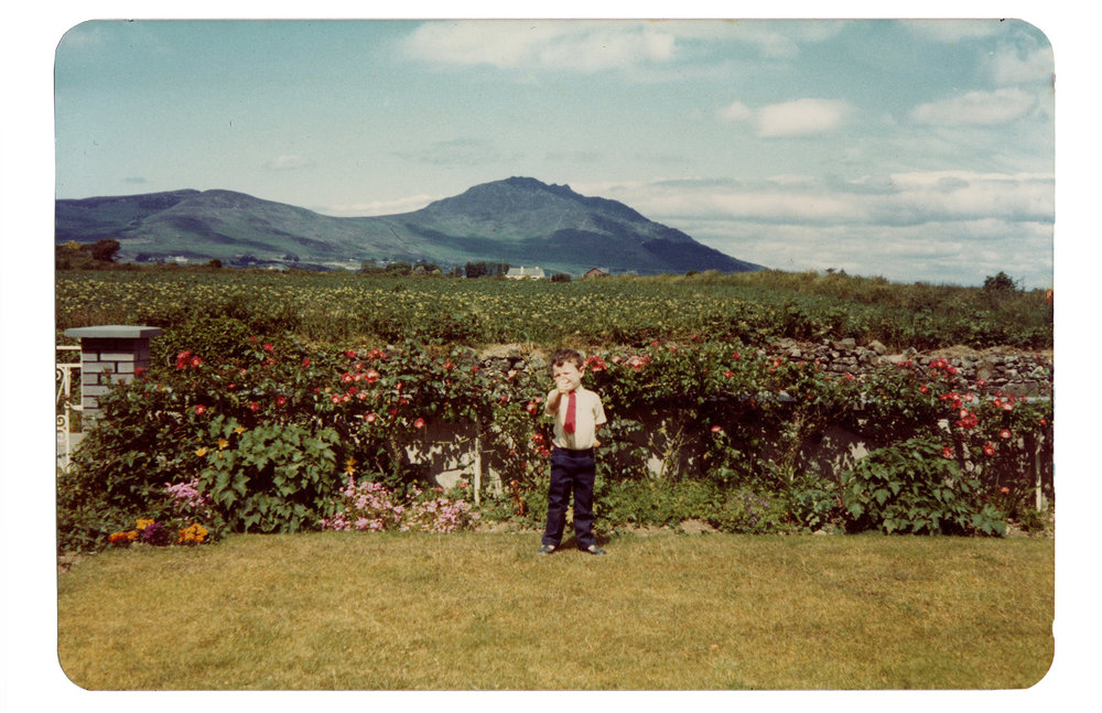 Standing in my late grandparents' front yard (Ireland, circa 1986) with Slieve Foy and the mythologically charged Cooley mountains in the background.