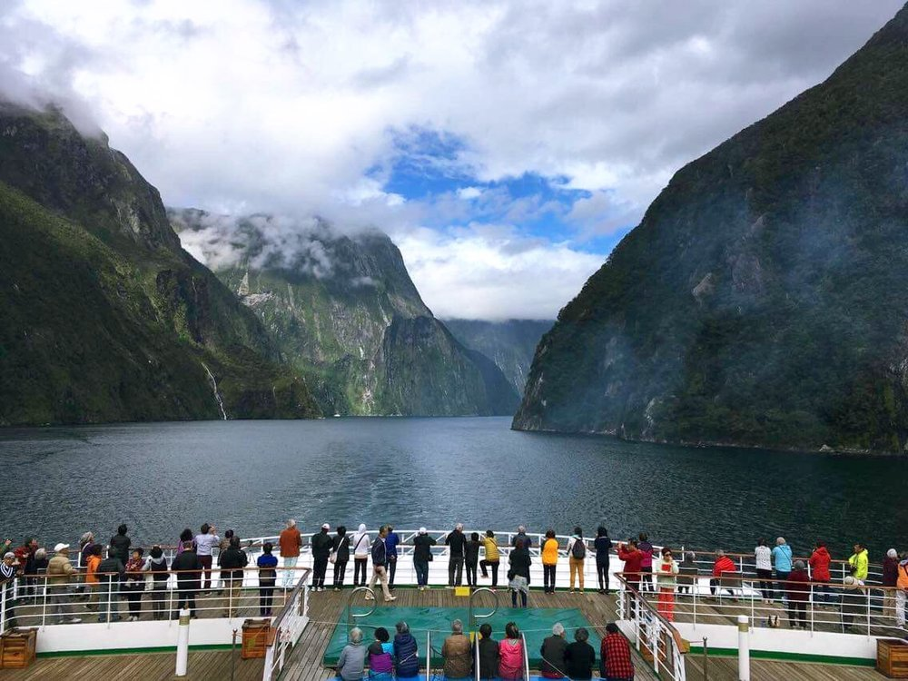 Picturesque panorama of Milford Sound from Peace Boat by Edu Villa   A Japan-based international NGO and NPO that promotes peace, human rights and many other social causes through its main activities on global peace voyages. This inspirational photo is shared by free-spirited Edu, a Global English Teaching programme coordinator of Peace Boat, whose mission is to spread the peace message and joy for language learning around the world. On Peace Boat's 96th voyage, the ship sailed through the magical Fiordland National Park with a spectacular fusion of mountains, waterfalls and wildlife.
