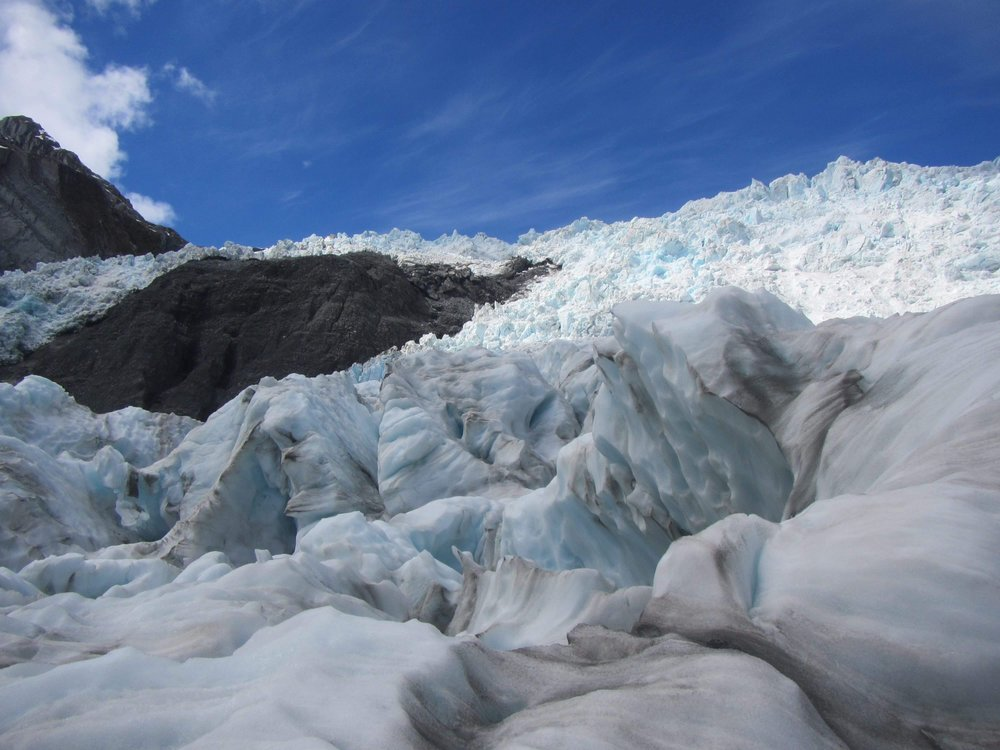 Franz Josef Glacier by  Yoshitaka Minami    A magnificent World Heritage area located in the Westland Tai Poutini National Park on New Zealand's South Island. Franz Josef's cloak of ice once flowed from the mountains right to the sea. After eons of retreat, the glacier is hidden inland now. This stunning shot was captured by Yoshi who spent 10 months in New Zealand on the working holiday programme. The overwhelming natural beauty of the glacier is mirrored by Yoshi's overwhelming sense of adventure and resilience as he travelled all over New Zealand.