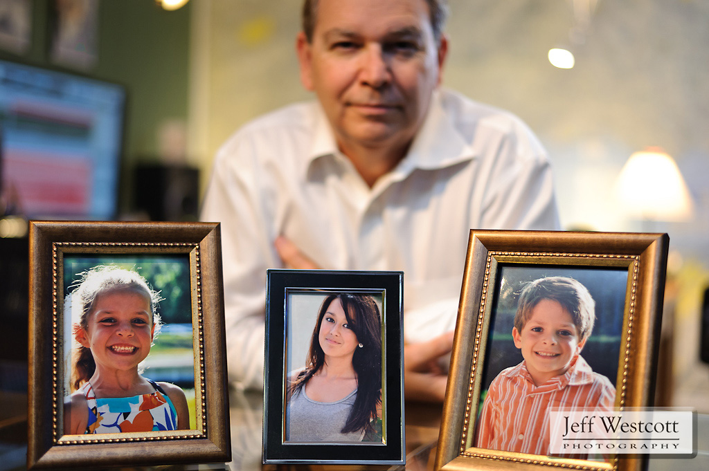 Steve Bowersox holds photos of his children Rachel (center), and twins Brooke and Ben.