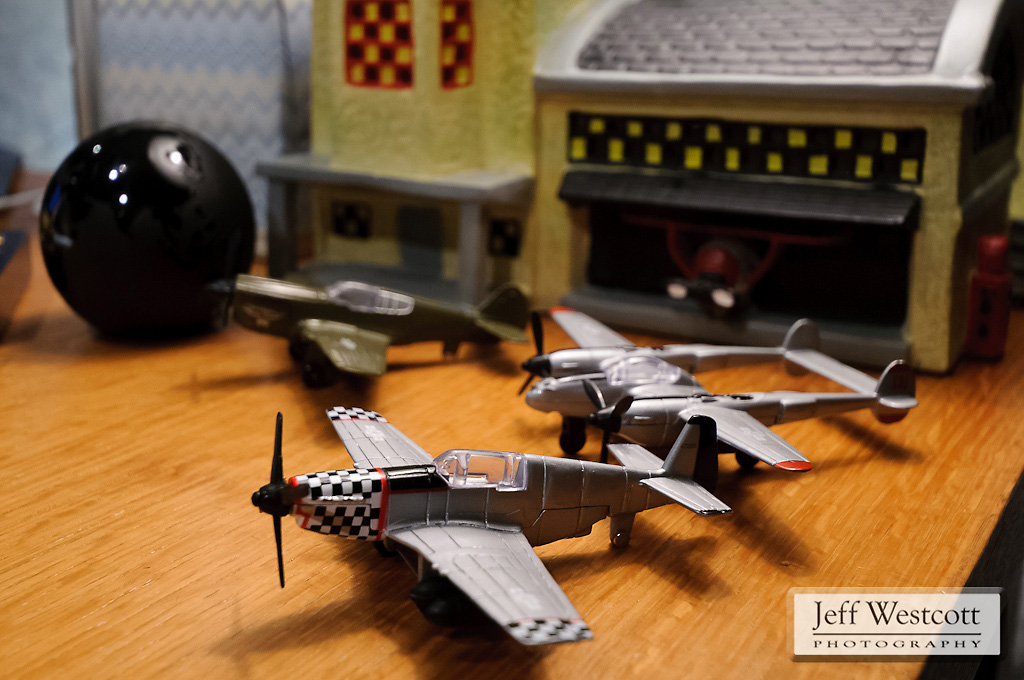 Toy airplanes sit in front of a model hangar and control tower on Steve Bowersox's desk.