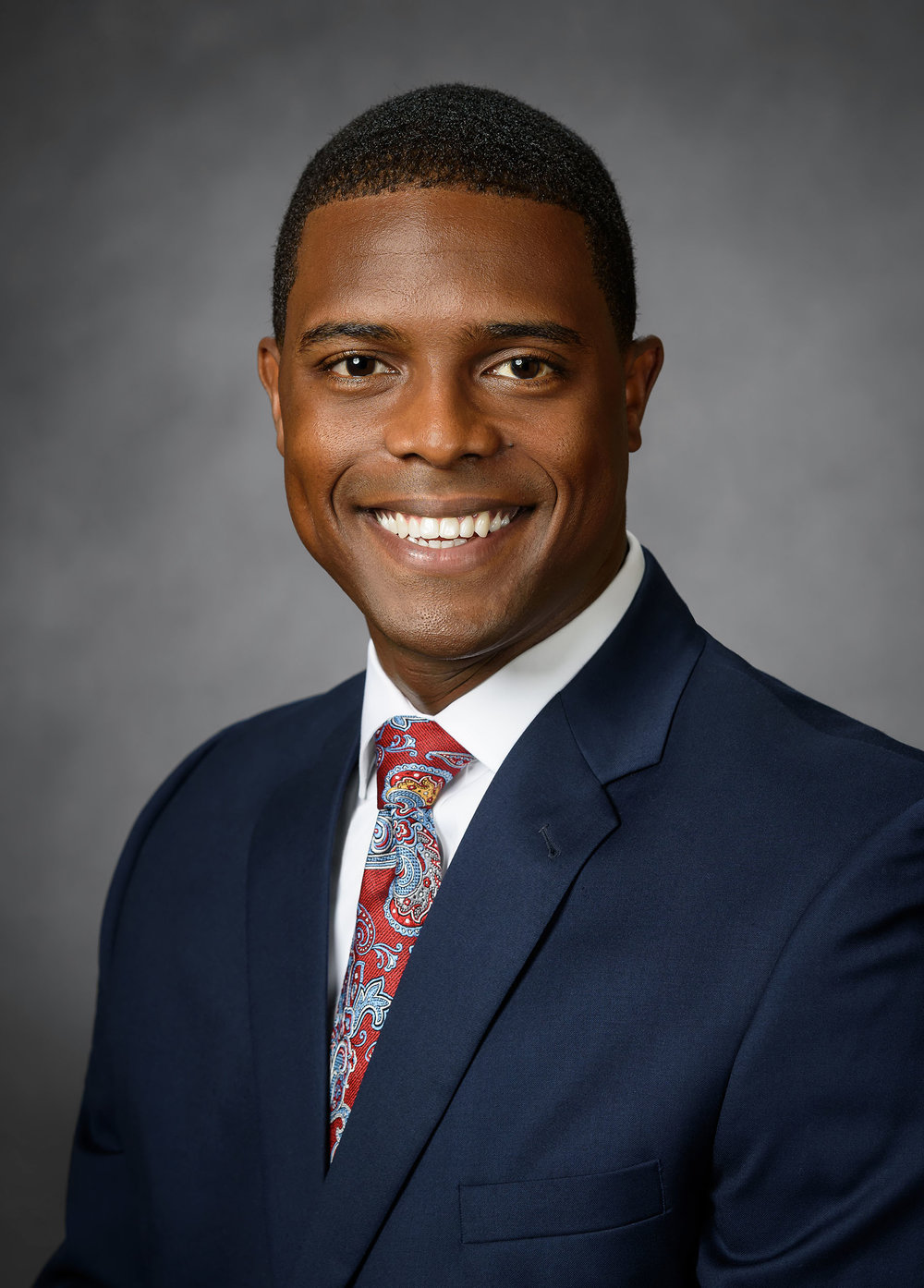 Executive headshot of Leo, a manager with the Cintas company. The medium-gray background works well with almost any clothing choice and any skin tone.