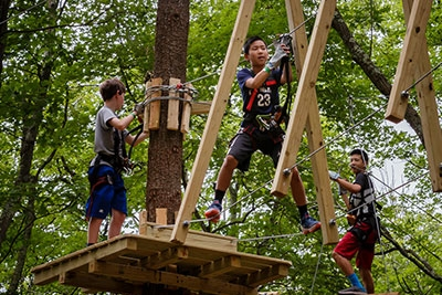 Three-boys-climbing-on-a-trail-tackling-obstacles.jpg