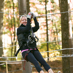 Woman zip-lining at TreeTop Adventures in Canton, MA