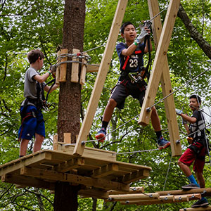 Three boys climbing on obstacles at TreeTop Adventures in Canton, MA