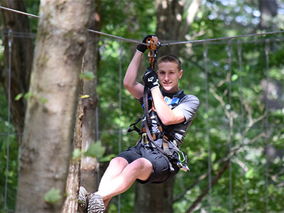 Young-man-zip-lining-past-the-trees-in-our-park,-TreeTop-Adventures-in-Canton,-MA.jpg
