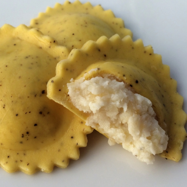 "Parmigiano Reggiano Agnolotti - Black Pepper Pasta   Medium 2"" Oval (35-37 per lb.) - 10 lb. Bulk  Parmigiano Reggiano, blended with Ricotta, Grana Padano & Parmesan Cheeses surrounded by a medium oval of our egg pasta flecked with black pepper."