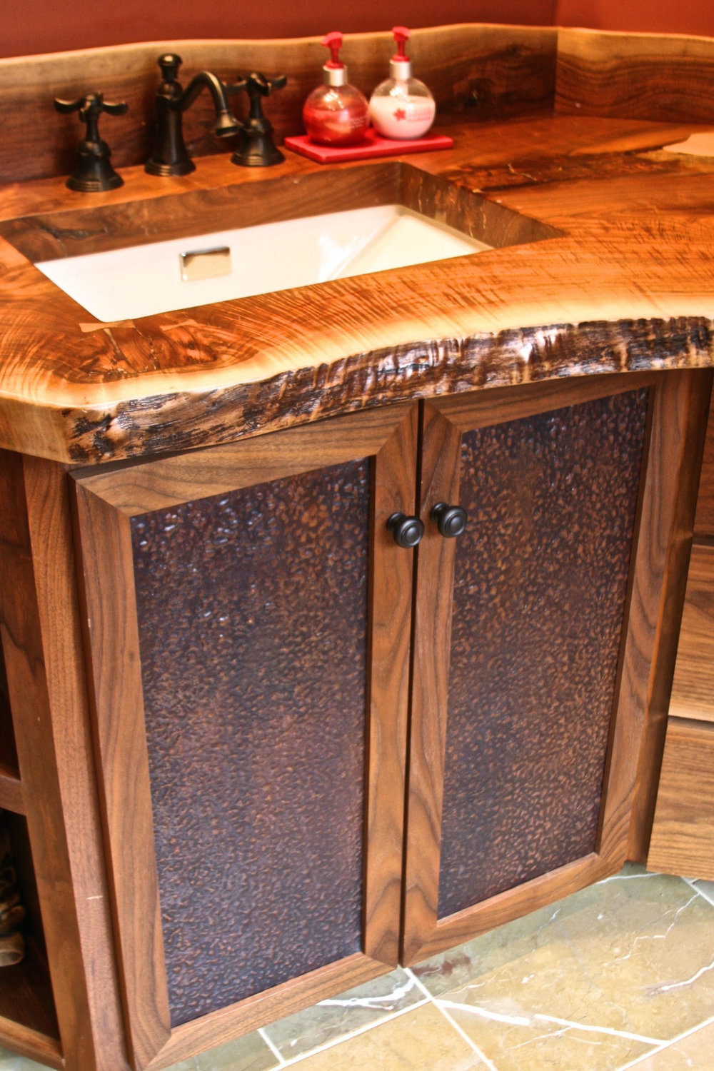 walnut vanity with walnut slab top and hammered copper panels.jpg