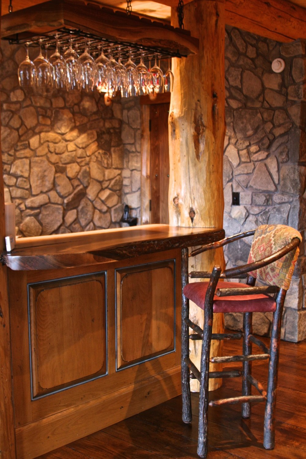 Custom bar with raised panel front, walnut slab top and our hickory hoop barstool.