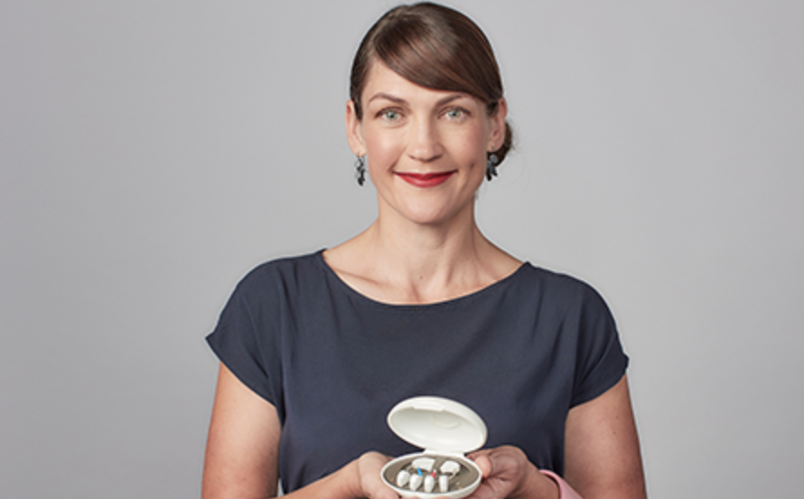 Designer Leah Heiss holding Facett (in its charging pod), the world's first modular, self-fit hearing aid