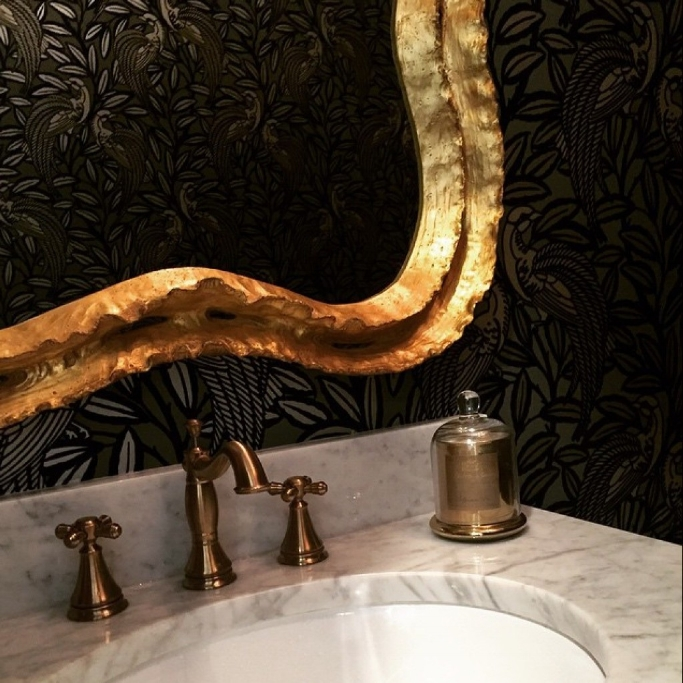 Black botanical wallpaper in a bathroom with gold mirror and marble. Design by Jillian O'Neill.