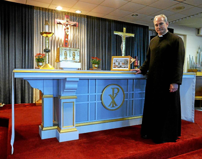 Father Jason stands next to the altar on which Pope Francis celebrated Mass on the Benjamin Franklin Parkway during his 2015 visit to Philadelphia for the World Meeting of Families.  The altar is now located at Holy Martyrs.