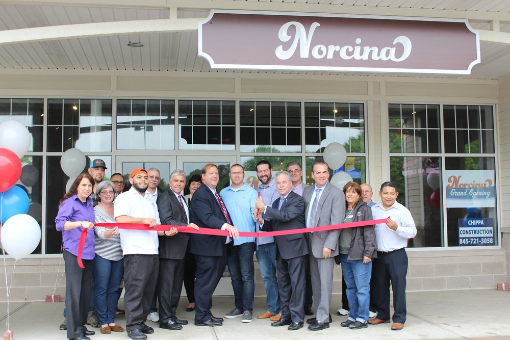 Owners Erick Carrasco (executive chef), Milan Dobrilovic, and Nick Nuccio celebrate Norcina's grand opening ribbon cutting ceremony with County Executive Ed Day, Town Supervisor George Hoehmann, Councilman Frank Borelli, Judge Scott Ugell and others on May 22, 2018.
