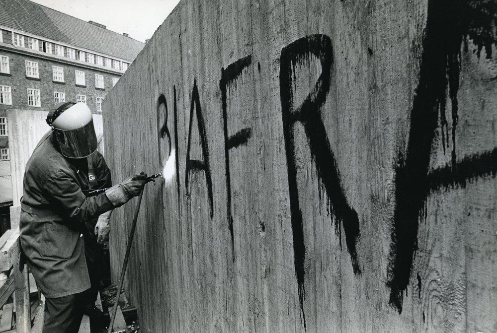 Vuosien 1967–1970 Biafran kansannousu ja -sota olivat Vietnamin sodan ja Prahan kevään ohella aikansa puhuttelevimpia kansainvälisiä selkkauksia, ja HYYn sympatia oli Biafran puolella. 1969 Temppeliaukion kirkon seinästä poistettavan graffitin tekijää ei tiedetä, mutta katseet olivat kääntyneet Leppäsuolle päin.  Kuva: HYYn arkisto/Ylioppilaslehti, 1969.