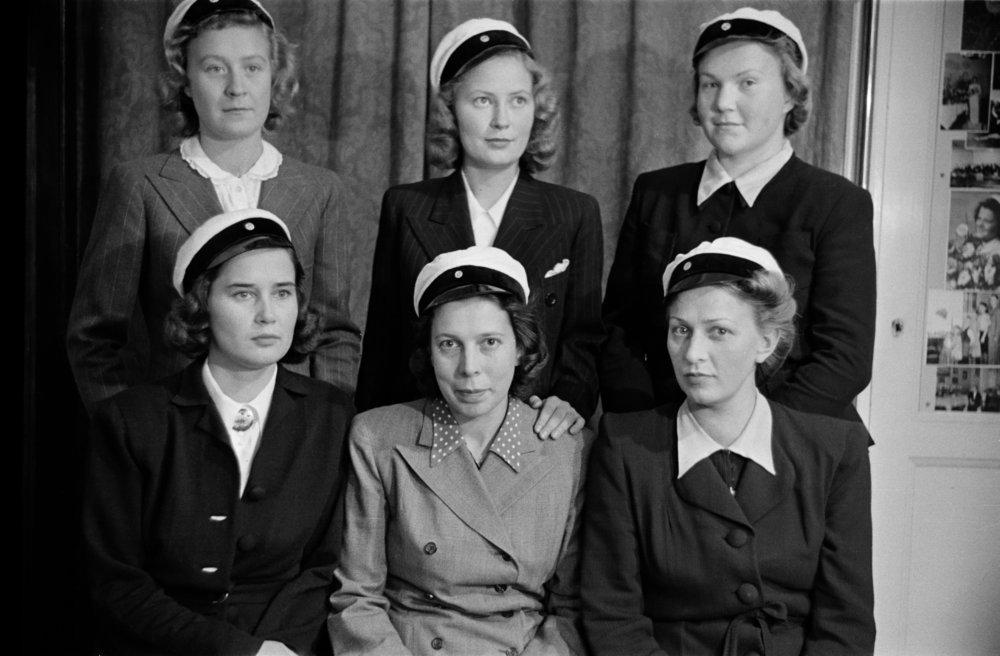 Naisten määrä yliopistolla kasvoi tasaisesti 1900-luvun alusta lähtien ja ylitti ensimmäisen kerran miesten määrän vuonna 1948. Tosin naiset usein keskeyttivät opintonsa mentyään naimisiin ja perustettuaan perheen vielä 1940- ja 1950-luvuilla. Kuvassa kuusi naisylioppilasta 1940-luvun ateljeekuvassa.  Kuva: Väinö Kannisto, 1945 / Helsingin kaupunginmuseon kokoelma.