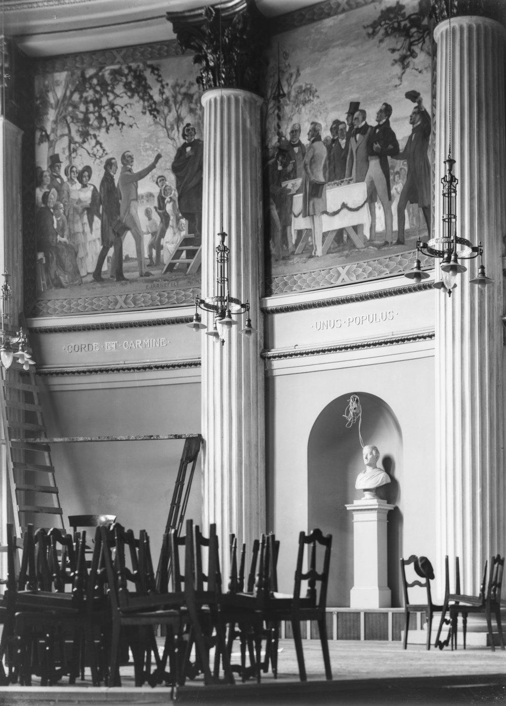 Eero Järnefeltin vuoden 1848 Floran päivän juhlaa kuvaava maalaus valmistui yliopiston juhlasaliin vuonna 1920. Kuvassa Fredrik Cygnaeus pitää kuuluisaa puhettaan ylioppilaille. Maalaus tuhoutui vuoden 1944 pommituksissa.   Kuva: Harald Rosenberg 1920 / Helsingin kaupunginmuseo