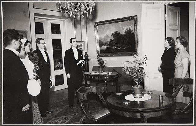 Promovendit pyytävät gratisti V. H. Sjöblomin johdolla neiti Leea Vannasta yleiseksi seppeleensitojaksi valtiotieteellisen tiedekunnan ensimmäiseen promootioon vuonna 1950.  Kuva: Museovirasto - Musketti, 1950